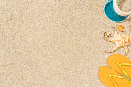 Photo for flat lay with arrangement of seashells, yellow flip flops and blue cap on sand - Royalty Free Image