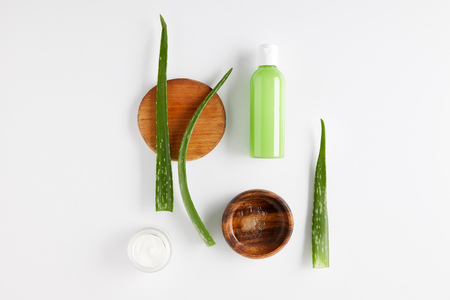 Foto für top view of wooden bowl with aloe vera juice, organic cream and shower gel, aloe vera leaves on wooden slices - Lizenzfreies Bild
