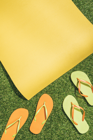 Photo for flat lay with yellow mat and flip flops on green grass - Royalty Free Image