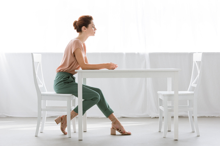 Photo pour side view of attractive young woman sitting at table alone at home - image libre de droit