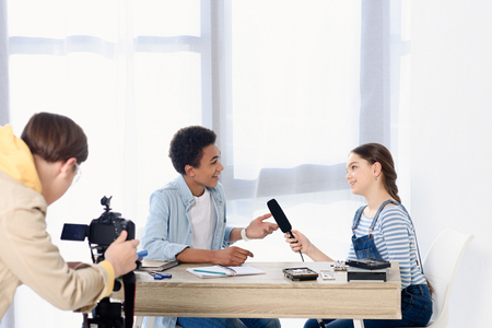 Photo pour caucasian teen kid conducting interview with african american friend for video blog - image libre de droit
