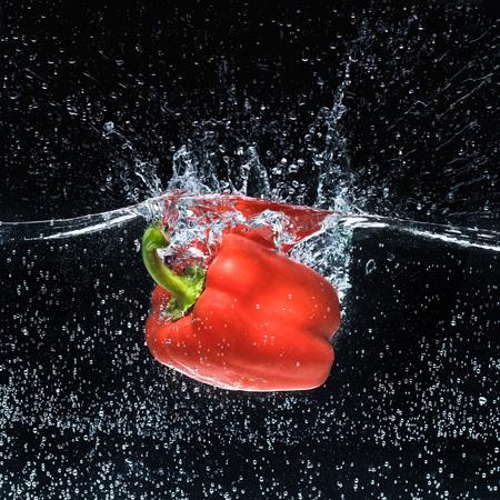 Foto de close up view of ripe red bell pepper in water isolated on black - Imagen libre de derechos