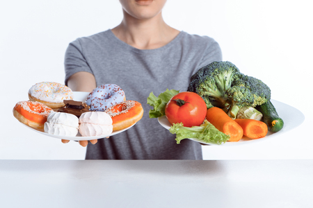 Photo pour cropped shot of woman holding plates with sweets and vegetables - image libre de droit