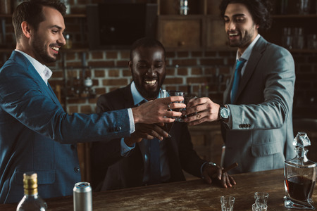 Photo pour cheerful young male friends in suits clinking glasses of whiskey - image libre de droit
