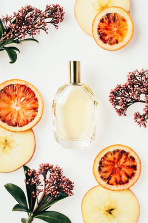 Photo pour top view of glass bottle of perfume surrounded with fruits and flowers on white - image libre de droit