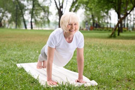 Photo pour smiling elderly woman doing plank on yoga mat on lawn - image libre de droit