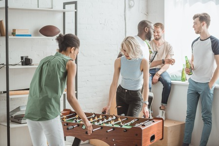 Photo for young women playing table football with male friends standing behind - Royalty Free Image