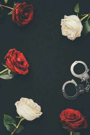 Photo for Metal handcuffs with rose flowers isolated on black - Royalty Free Image