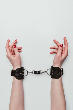 Photo for Female hands tied with leather handcuffs isolated on white - Royalty Free Image