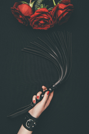 Photo for Black leather flogging whip in female hand by red roses isolated on black - Royalty Free Image