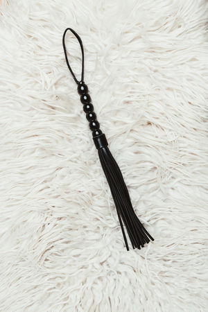 Photo for Black leather flogging whip on white carpet - Royalty Free Image