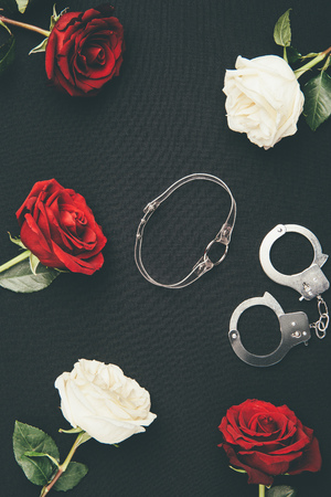 Photo for Collar and handcuffs with rose flowers isolated on black - Royalty Free Image