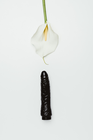 Photo for Black dildo with white calla flower isolated on white - Royalty Free Image