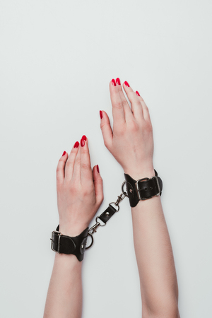 Photo for Black leather cuffs on female hands isolated on white - Royalty Free Image