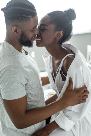 Photo pour side view of smiling african american boyfriend kissing girlfriend at kitchen - image libre de droit