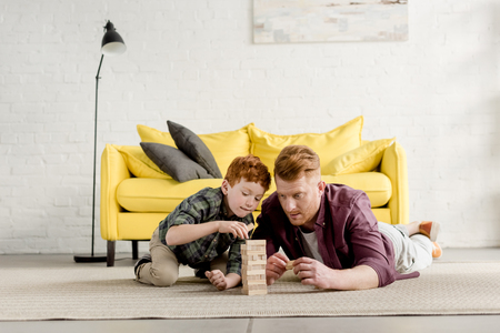 Foto de concentrated redhead father and son lying on carpet and playing with wooden blocks at home - Imagen libre de derechos