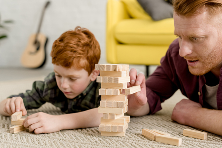 Foto de cropped shot of concentrated father and son building towers from wooden blocks at home - Imagen libre de derechos