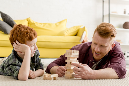 Foto de happy redhead father and son playing with wooden blocks at home - Imagen libre de derechos