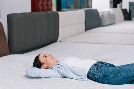Foto de side view of smiling customer lying on orthopedic mattress in furniture store - Imagen libre de derechos