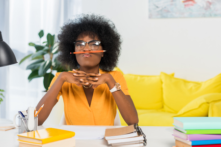 Photo pour portrait of african american freelancer in eyeglasses with pencil at workplace at home office - image libre de droit