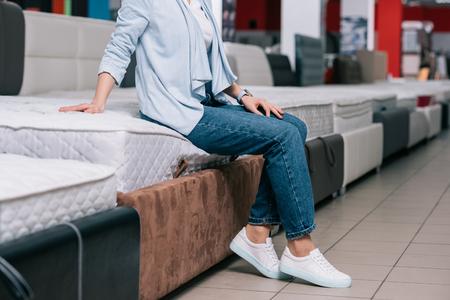 Foto de partial view of woman sitting on mattress in furniture shop - Imagen libre de derechos