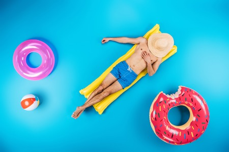 Foto de top view of young man in shorts resting on inflatable mattress on blue, summer vacation concept - Imagen libre de derechos