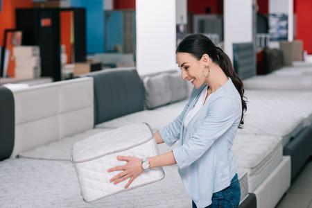 Foto de smiling woman with folding mattress in hands in furniture shop - Imagen libre de derechos