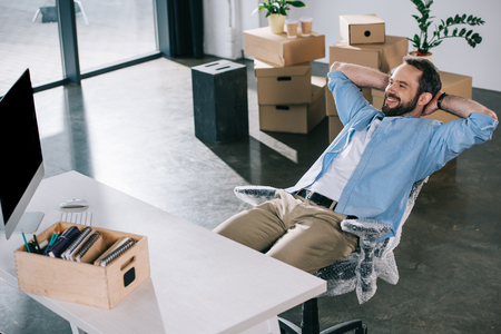 Photo for happy businessman sitting with hands behind head and looking away in new office during relocation - Royalty Free Image