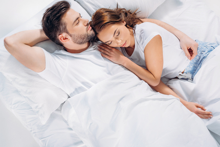 Photo for overhead view of young couple sleeping in bed together - Royalty Free Image