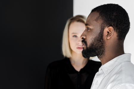 Foto für side view of handsome african american boyfriend standing in front of blonde girlfriend - Lizenzfreies Bild
