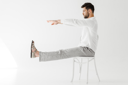 Foto de side view of male model in linen clothes sitting on chair with outstretched legs and hands isolated on grey background - Imagen libre de derechos