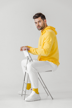 Photo pour side view of handsome young man in yellow hoodie sitting on chair on white - image libre de droit