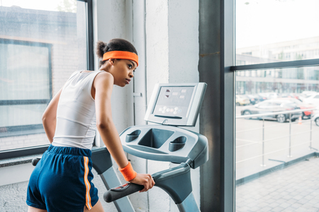 Photo pour young african american female jogger running on treadmill at gym - image libre de droit