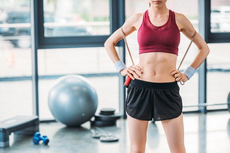 Photo pour partial view of sportswoman with skipping rope standing akimbo at gym - image libre de droit