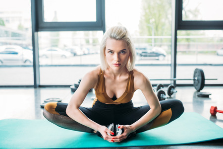 Photo pour young athletic woman stretching on fitness mat at gym - image libre de droit