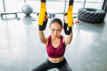 Photo pour high angle view of asian female athlete training with resistance bands at gym - image libre de droit