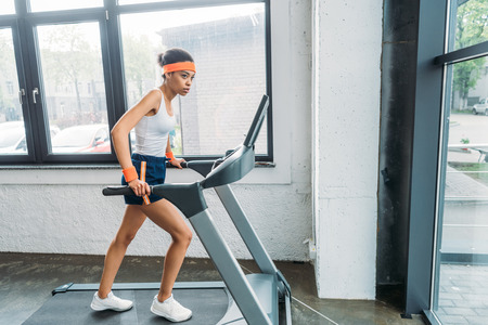 Photo pour african american female athlete running on treadmill at gym - image libre de droit