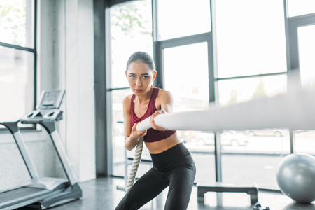 Photo pour young asian sportswoman working out with battle rope at gym - image libre de droit