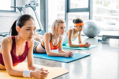 Photo pour multicultural female athletes exercising on fitness mats at gym - image libre de droit