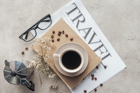 Foto de top view of delicious coffee on book and newspaper with travel inscription on concrete surface - Imagen libre de derechos
