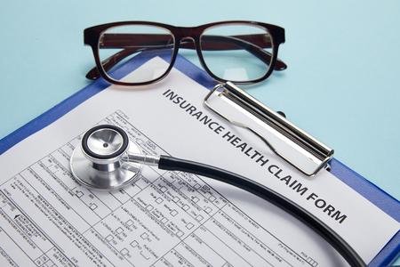 Photo pour insurance health claim form, clipboard, eyeglasses and stethoscope on blue - image libre de droit