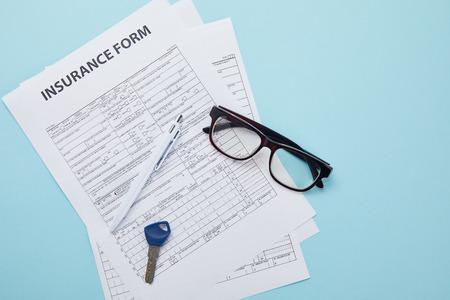 Photo pour top view of insurance form, eyeglasses, key and pen isolated on blue - image libre de droit