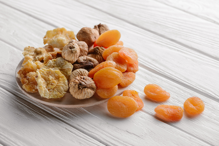 Photo for Mixed dried fruits on white plate on wooden table - Royalty Free Image