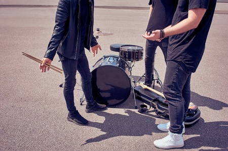 Photo for partial view of rock band in black clothing standing near musical instruments on street - Royalty Free Image