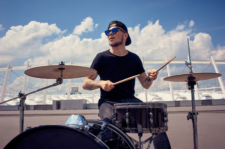 Photo for young tattooed drummer in sunglasses playing drums on street - Royalty Free Image