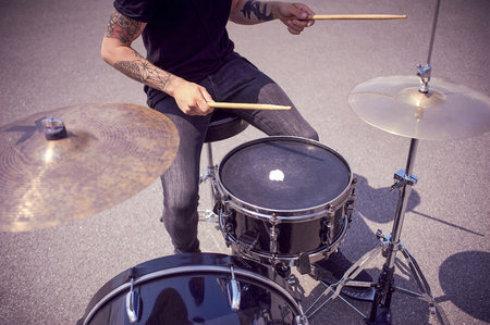 Photo for cropped shot of tattooed drummer playing drums on street - Royalty Free Image