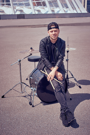 Photo for drummer in black clothing with drum sticks sitting on drum kit on street - Royalty Free Image