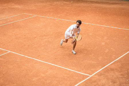 Photo pour handsome tennis player training with wooden racket on brown court - image libre de droit