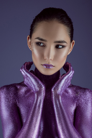 Photo pour stylish attractive asian girl in ultra violet glitter, isolated on purple - image libre de droit