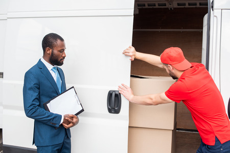 Photo for african american businessman with notepad looking at caucasian delivery man closing van with cargo - Royalty Free Image